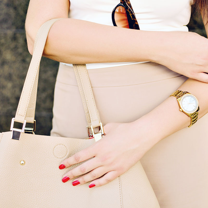 Woman Holding A Beige Purse